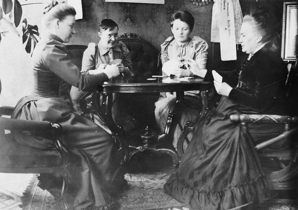 Neljä naista pelaamassa Skruuvipeliä pöydän ääressä Kanttilan salongissa. Henkilöt vasemmalta Hanna Guseff, Alma Tervo, Maiju Canth ja Minna Canth vuonna 1890-1896.