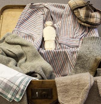 Hellahuoneen Paavo -laukussa on pieni pieni kipsinen ihmishahmo vaatteiden keskellä.