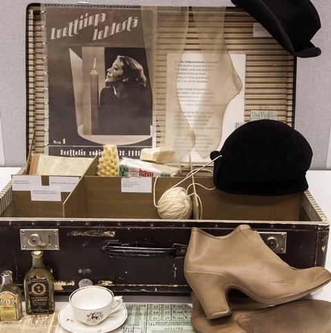 Musta salkku, jonka sisällä hattuja, lankarullia, mäntysuopaa ja edustalla korkokengät, kahvikuppi ja tassi, pieniä pulloja.