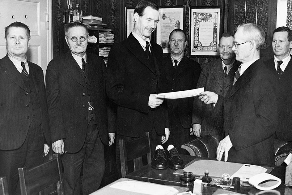 Mestari- tai kisällikirjan luovutus v. 1940-1949. Kengällä pöydät, jotka on arvioitu ja joiden perusteella todisteeksi osaamisesta on myönnetty mestari- tai kisällikirja. Kuva: KUHMU