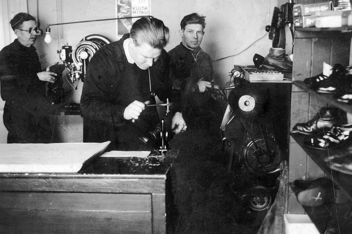 Korhosen jalkineliike Kauppakadun ja Savonkadun kulmassa. Kuvassa Itkonniemeläinen suutari Jussi Pirskanen työssä v. 1938. Kuva: KUHMU