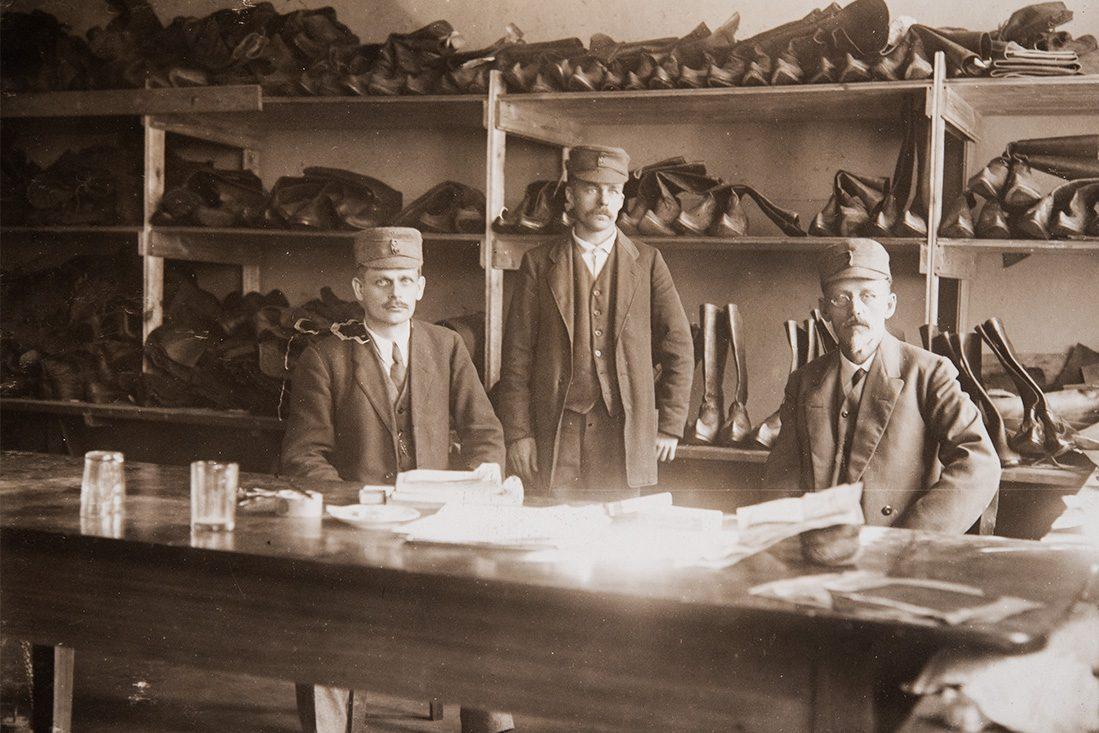 """Вероятно, члены Охранного корпуса. Сапожник А.Копонен и образцы обуви """"лапикас"""" с загнутыми концами. Щюцкоровцы пользовались сапогами или традиционной финской обувью. Снимок: КУХМУ"""