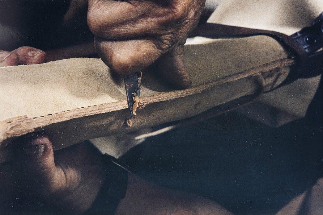 Kun varren takasauma on ommeltu, tasoitetaan sisäsauma veitsellä v. 1982. Kuva: Kari Jämsén / KUHMU