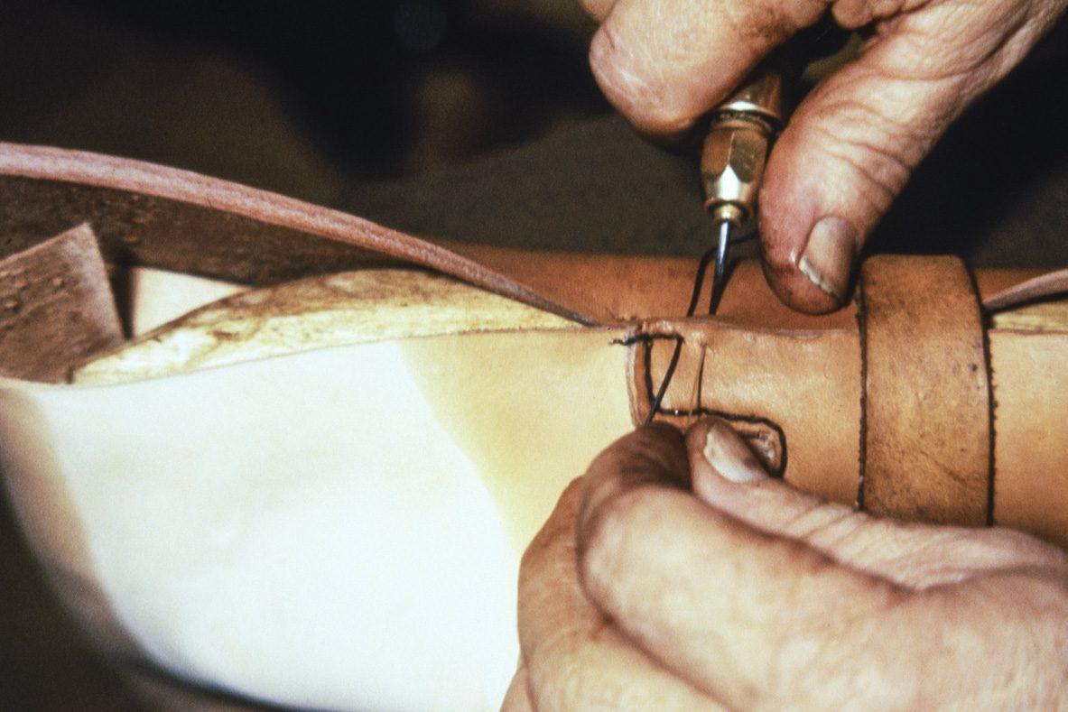 Kengän sivut (ääret) kiinnitetään kengän päälliseen (kauto). Ensimmäinen ompelukerta (ohutommel) tehdään 3-säikeisellä pikilangalla v. 1978. Taitava suutari pystyy tekemään tämänkin ompelutelineellä – aloittelijan on helpompi käyttää lestiä. Kuva: Juha Miettinen / KUHMU
