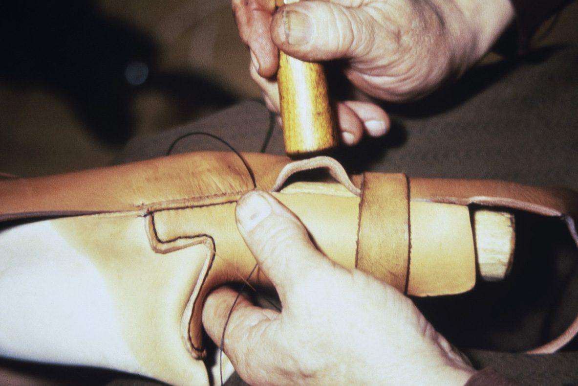 Kengän sivujen väljyys poistetaan kutistamalla kostutettua nahkaa v. 1978. Kuva: Juha Miettinen / KUHMU