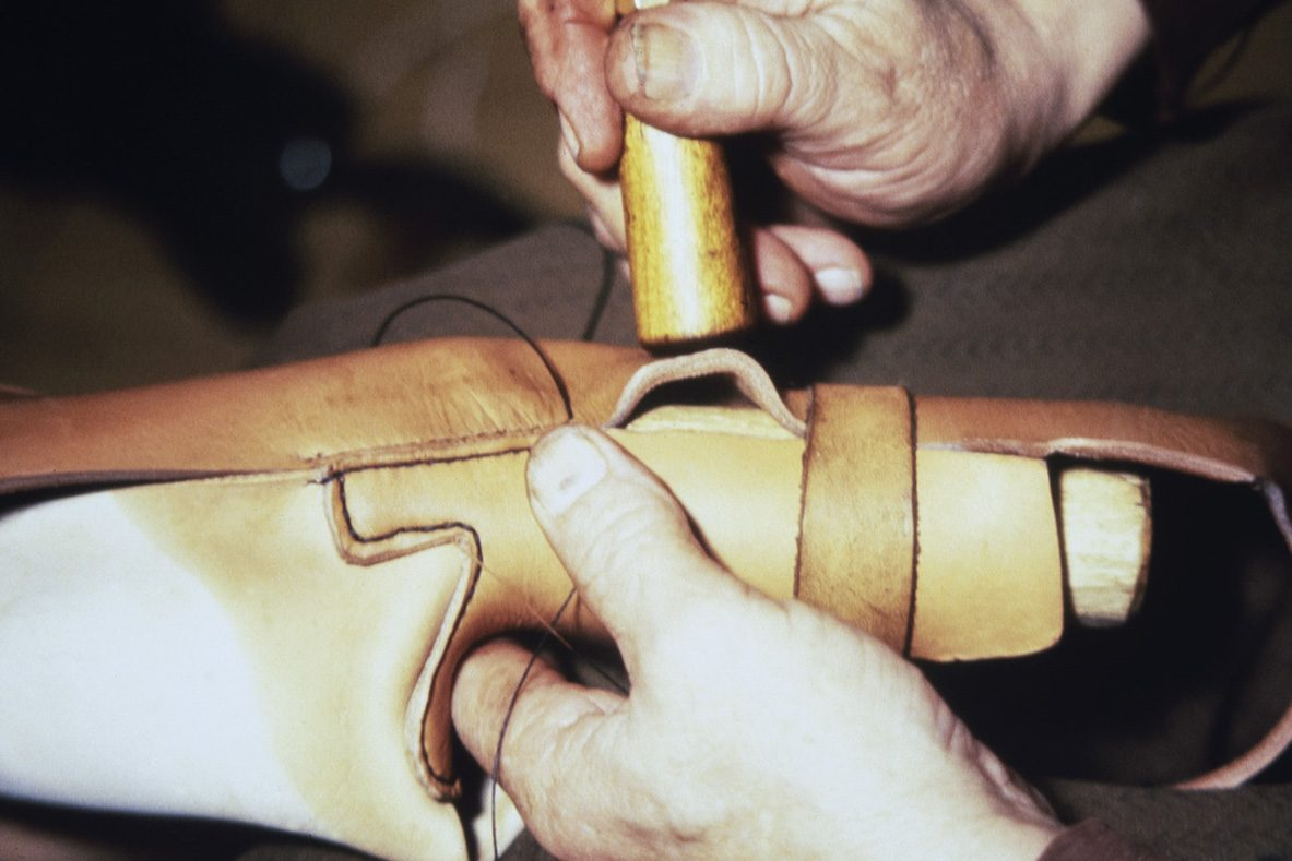 The loose fit of the shoe is removed by shrinking dampened leather, 1978. Photo: Juha Miettinen / KUHMU