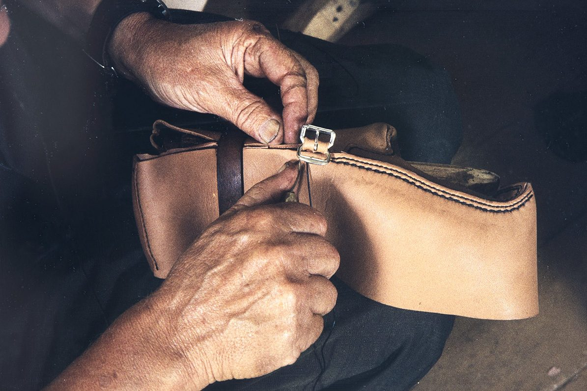 When sewing the ankle part, the buckle is sewn at the same time to the seam, 1982. Photo: Kari Jämsén / KUHMU