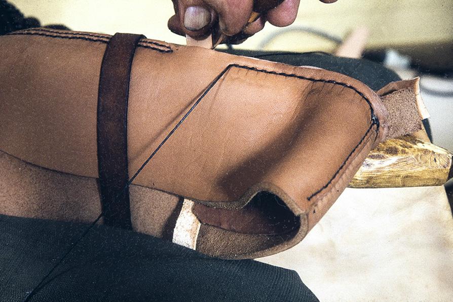 Nilkan toiselle puolen ommellaan remmi, joka kiinnitetään solkeen v. 1982. Kuva: Kari Jämsén / KUHMU