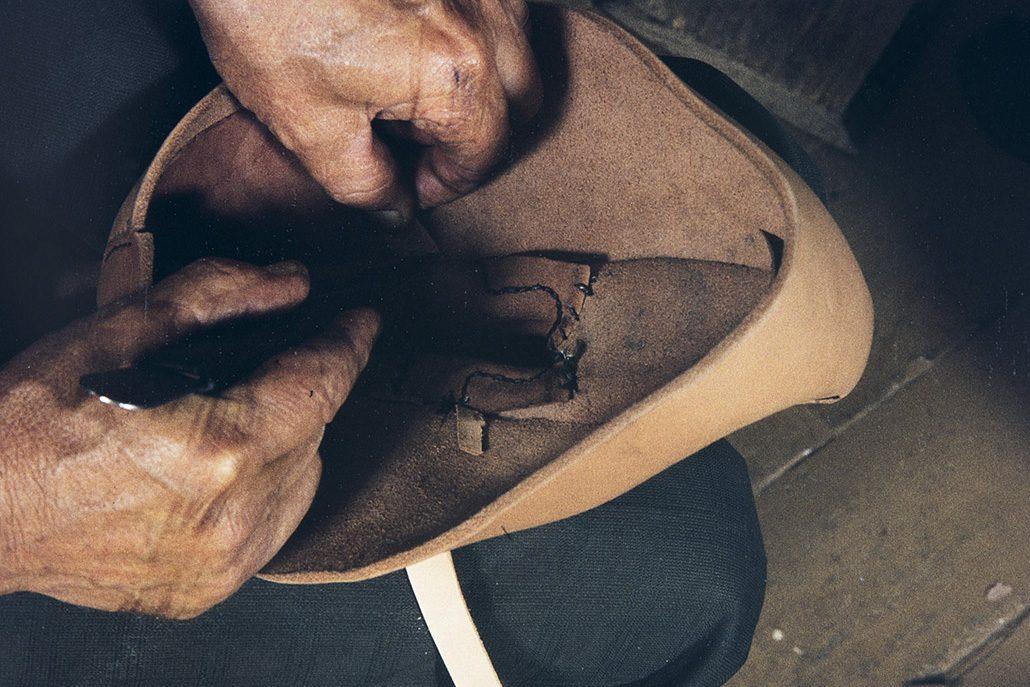 Nilkan ompelulangat päätellään nilkan sisään ja solkiremmien päät leikataan sisältä pois v. 1982. Kuva: Kari Jämsén / KUHMU