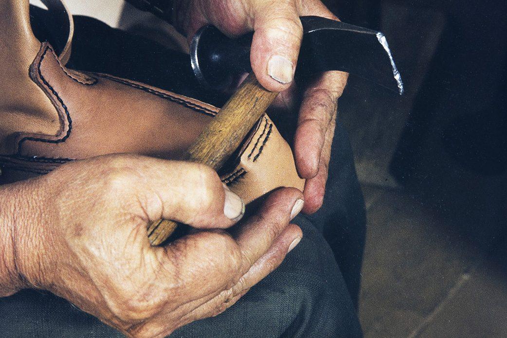 Kengän laittamisessa lestille voi käyttää apuna vasaraa v. 1982. Kuva: Kari Jämsén / KUHMU