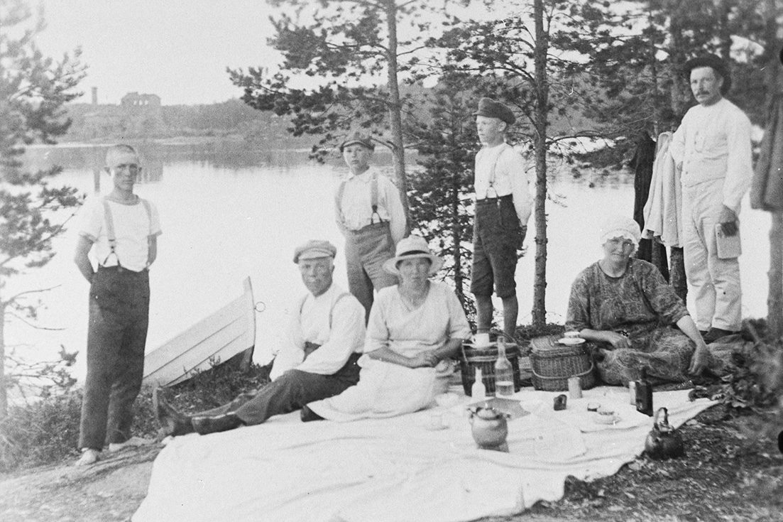 Coffee break on the beach, in the background the Souru Ironworks in Syväniemi, 1924-1930. Photo: H. T. Lehmusto / KUHMU
