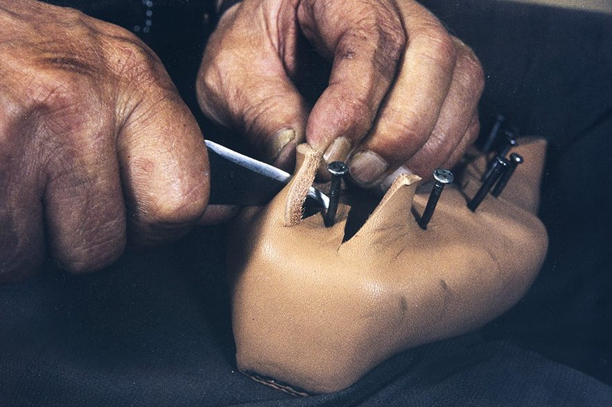 Kun pinnaus on valmis, leikataan kengän sivujen (äären) reunaan kolmiot v. 1982. Kuva: Kari Jämsén / KUHMU
