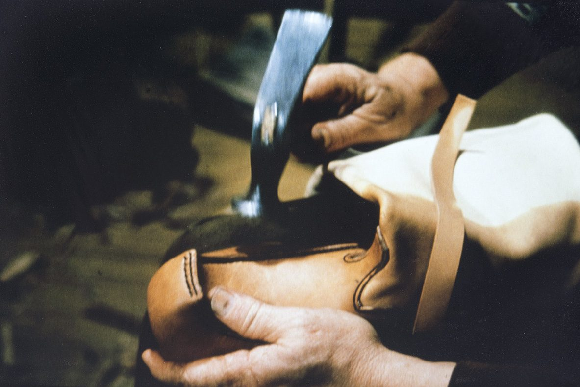 Kengän päällistä (kauto) ja kengän sivuja (ääriä) voi pinnausvaiheessa tasoitella lestille esimerkiksi vasaralla v. 1978. Kuva: Juha Miettinen / KUHMU