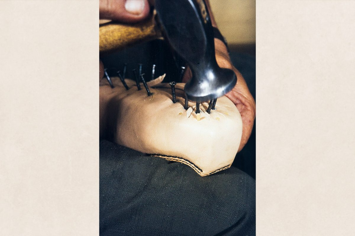 After drying the leather on the sides of the shoe, attach the sides of the shoe (edge) to the last with wooden nails, 1982. Photo: Kari Jämsén / KUHMU