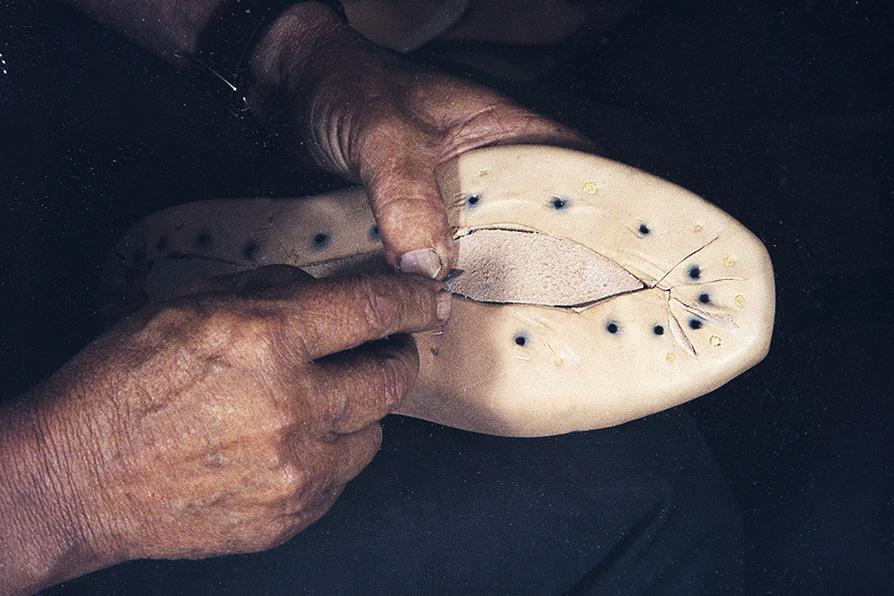 Pohjaan laitetaan tasoitenahka v. 1982. Jos kenkien haluttiin narisevan tai naukuvan, tähän osaan saatettiin laittaa myös tuohenpala tai leppälevy. Kenkien narina on ilmentänyt muun muassa varallisuutta. Narinan tekeminen oli suutarien ammattisalaisuus. Kuva: Kari Jämsén / KUHMU