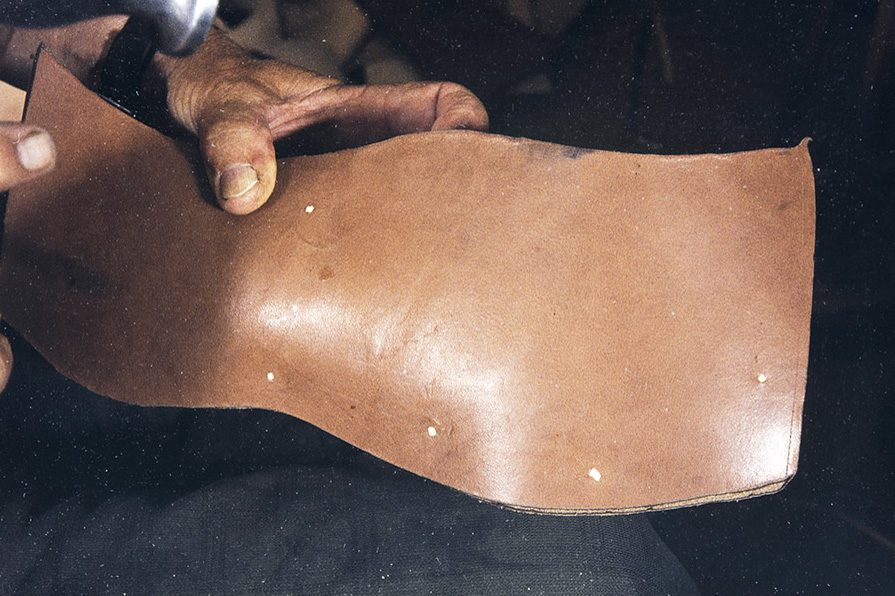 Кожа для подошвы закрепляется деревянными гвоздиками, 1982 г. Снимок: Кари Ямсен / КУХМУ