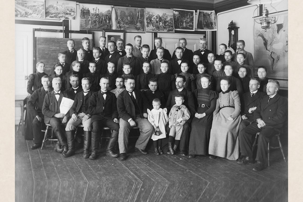 Group photo of North-Savo Folk High School students in Halola, Maaninka, 1896-1899. In the front row, seated on the left are wearing Finnish boots, the children in the front, button boots. In the photo, 1st row (from left): 5. Tellervo Mikander in front of Augusta Mikander 6. Aarne Mikander in front of Hjalmar Mikander. Photo: Victor Barsokevitsch / KUHMU