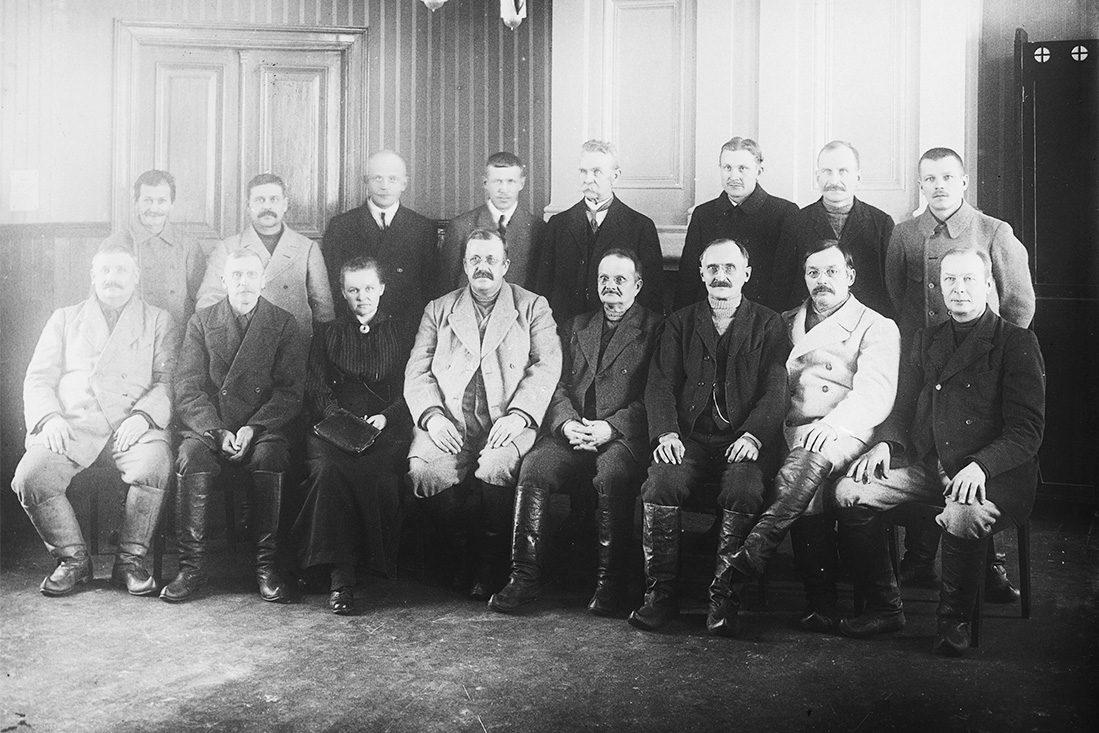 Kokous Kuopion maalaiskunnan talossa v. 1920-1923 Maljalahdenkatu 18:ssa. Usealla osanottajalla on jalkineina lapikkaat. Kuva: Victor Barsokevitsch / KUHMU