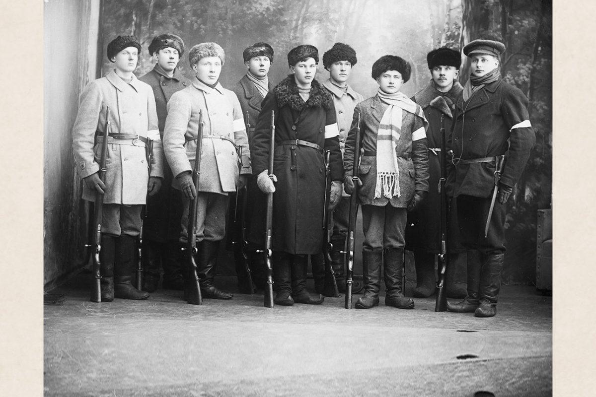 """Щюцкоровцы из Нильсия позируют в ателье Виктора Барсокевича, 1918 г. Многие из них одеты в сапоги """"лапикас"""" с загнутыми концами. Справа налево: Атте Пиринен, Вернери Лаппалайнен, Эйно Пентикяйнен, Ялмари Ниеми, Эмил Кокконен, Пекка Пиетикяйнен, Ханнес Пиетикяйнен, Юха Таскинен, Антти Таскинен. Снимок: Виктор Барсокевич / КУХМУ"""