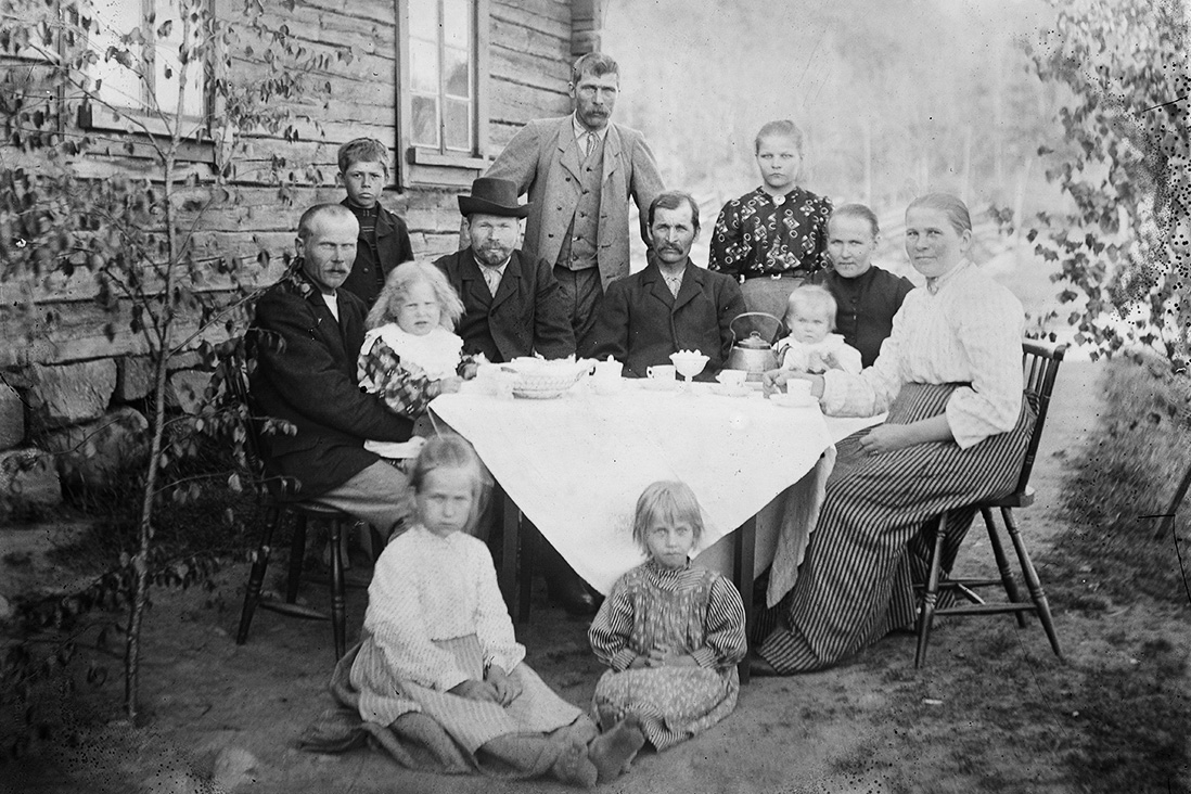 Midsummer coffee at Thurela (official name Vierunpää) in 1909 in Raiskio village in Riistavesi. In the photo, from left: Otto Mönkkönen, Kalle Miettinen, Kirsti Mönkkönen, Jussi Thure, Kalle Thure, Taavetti Thure, Anna Tuppurainen, Katri Thure, Helena Thure, Agatha Mönkkönen, Eeva Puustinen and Hilma Ropponen. Photo: Hilma Miettinen / KUHMU