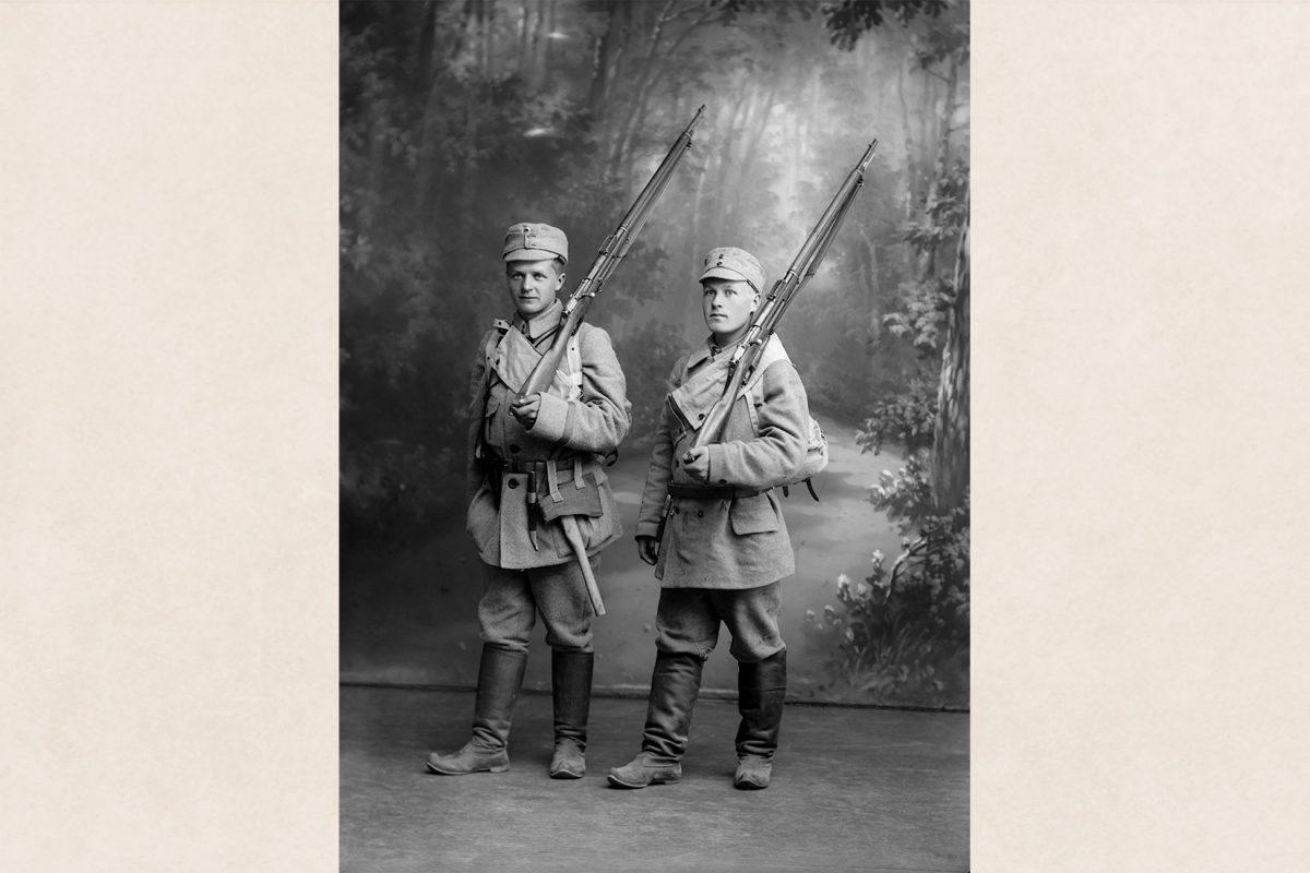 Kaksi sotilasta kuvattavana ateljeessa v. 1918. Sotilaspuvun jalkineina lapikkaat. Kuva: Victor Barsokevitsch / KUHMU