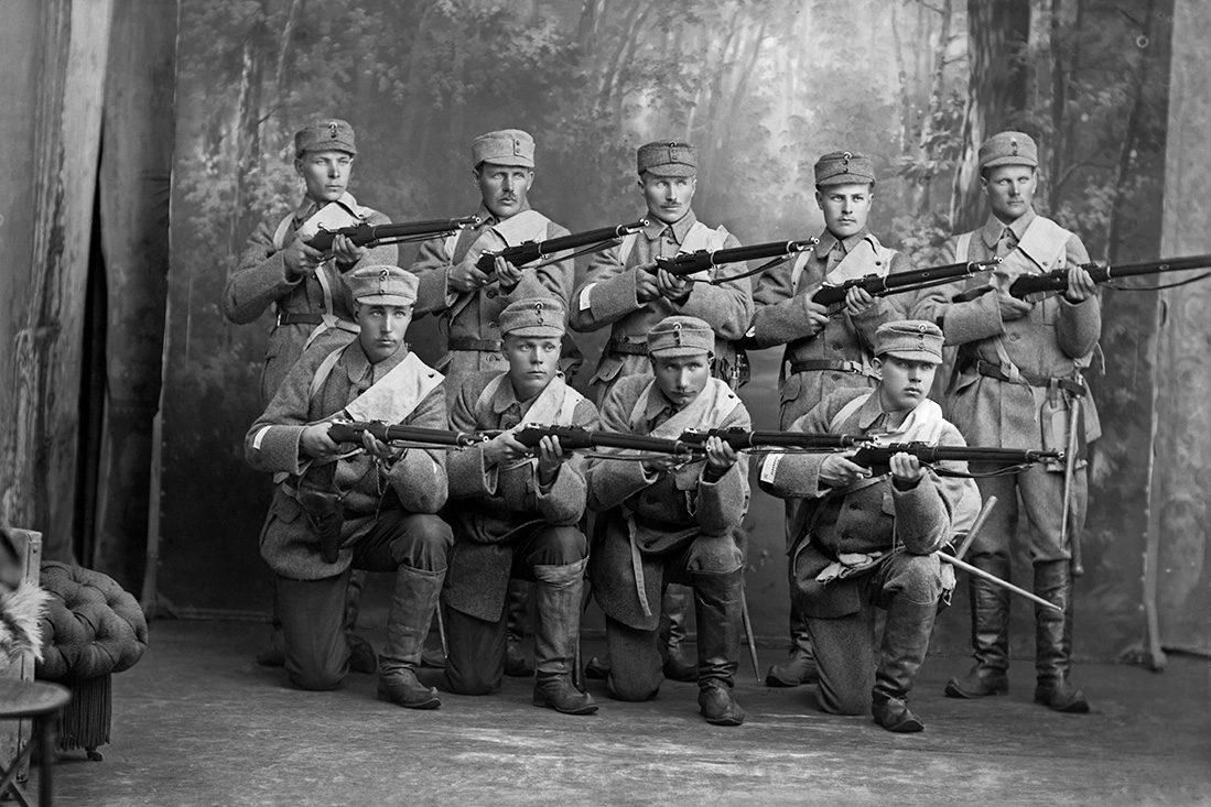 Мартти Боман и 8 солдат в ателье мастера светописи В.Барсокевича , 1918 г. Одеты в лапикасы. Снимок: Виктор Барсокевич / КУХМУ