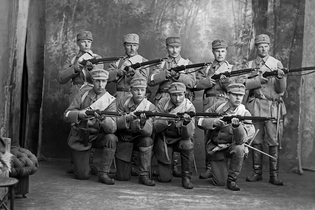 Martti Boman ja 8 muuta sotilasta Barsokevitschin kuvaamossa v. 1918. Sotilaspuvun jalkineina lapikkaat. Kuva: Victor Barsokevitsch / KUHMU