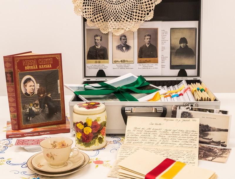 Minna Canth -oppimispaketti. Pöydällä oleva salkku, kirjaitä, kahvikuppi tasseineen, korttipakka ja Minna Canthin Köyhää Kansaa -kirja.