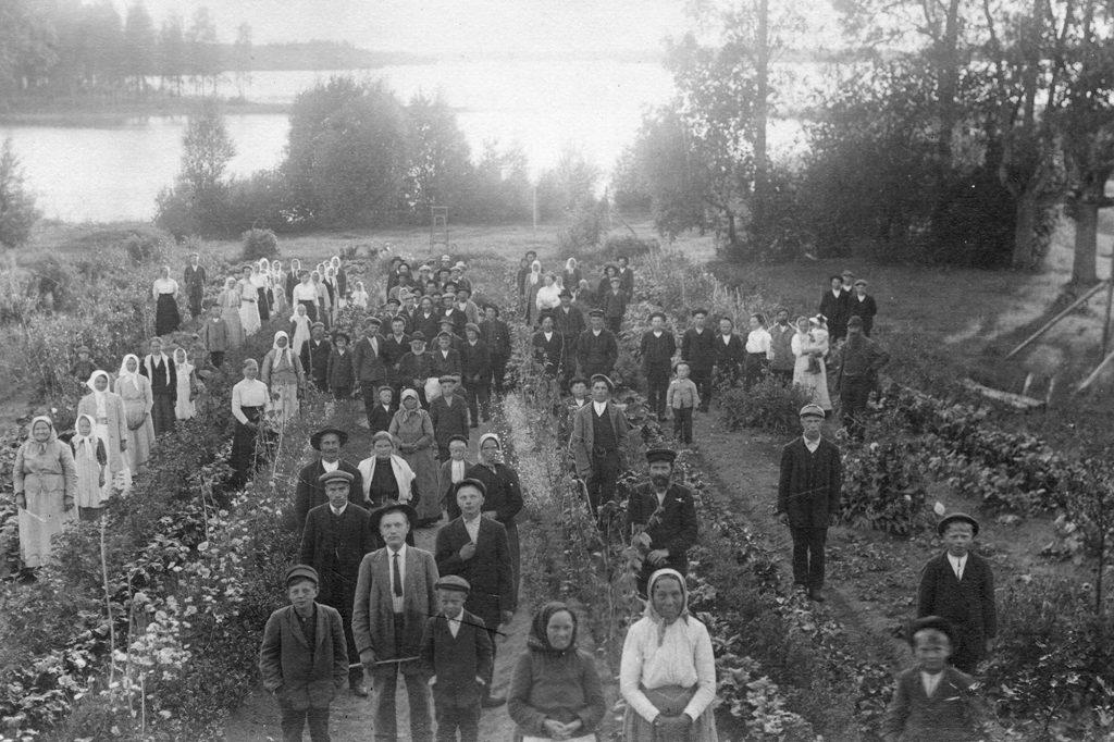 Paljon ihmisiä seisomassa pellolla ja kaikki katsovat kameraan. Kuva otettu ylhäältä päin.