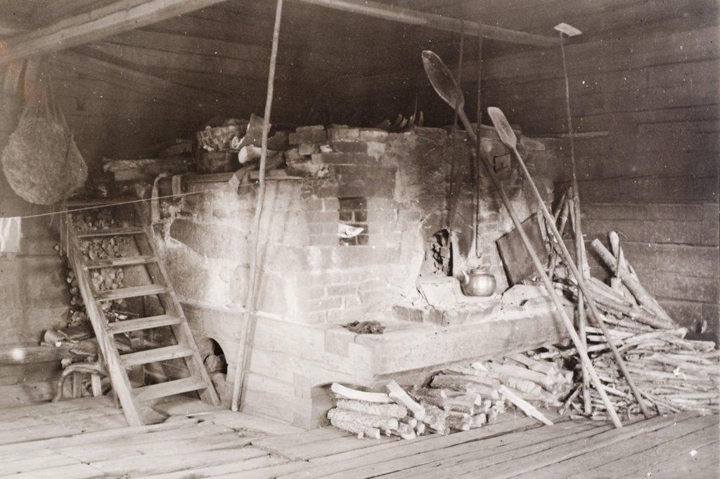 Seepian sävyisessä valokuvassa keskellä huonetta suuri vaalea uuni, jonka edustalla leipälapioita ja kahvipannu.
