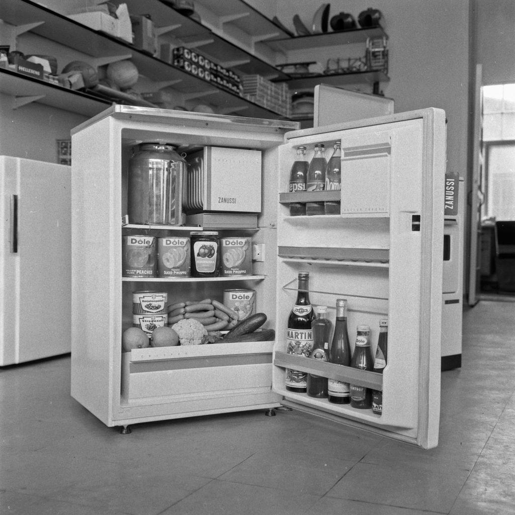 Jääkaappi mustavalkoisen kuvan keskellä. Hyllyt ovat täynnä ruokia.