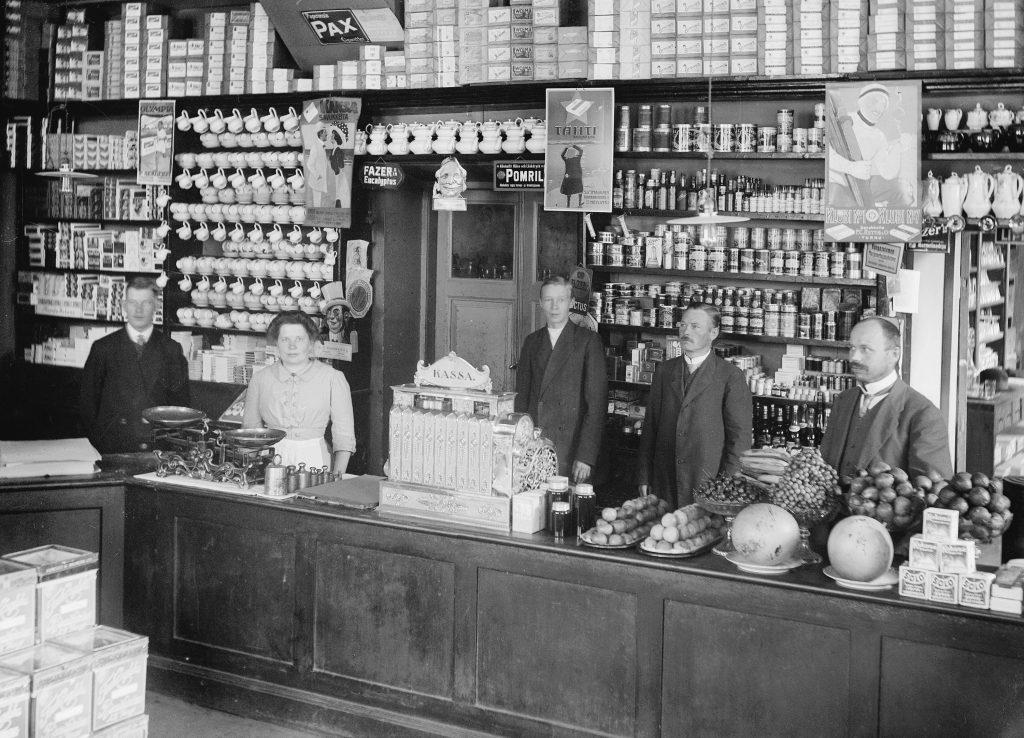 Kaupan työntekijät seisovat tiskin takana, hyllyt heidän takana notkuvat monenlaisia tuotteita. Mustavalkokuva.
