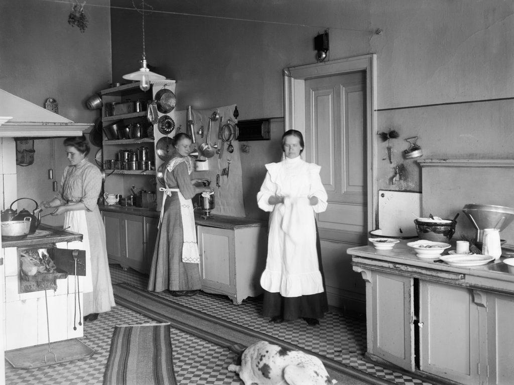 Palvelusväkeä keittiössä. Kuvan keskellä nainen kantaa pyyhettä valkoisessa asussa.