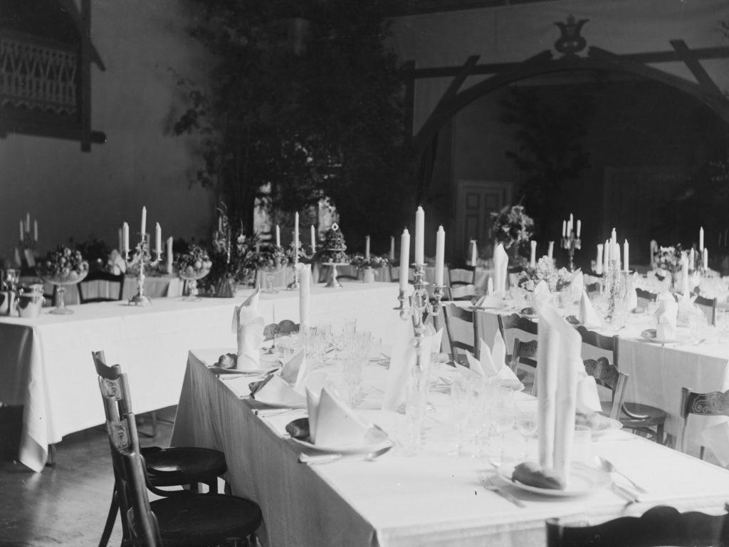 Kolme pitkää katettua pöytää mustavalko valokuvassa. Pöydissä valkoiset liinat ja servietit taiteltuna lautasten päälle. Keskellä pöytää kolmihaarainen kynttilänjalka.