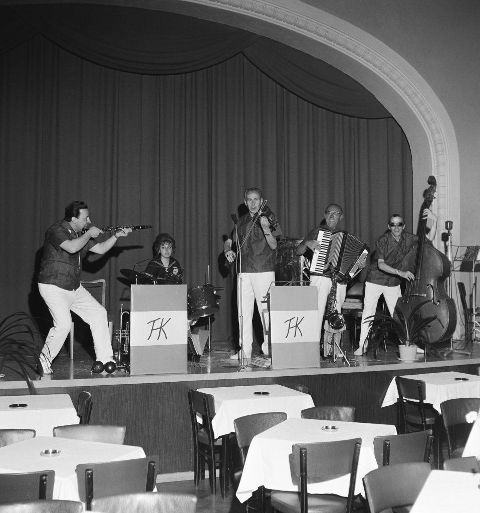 Orkesteri lavalla mustavalkoisessa kuvassa. Oikeassa laidassa basisti ja haitarinsoittaja. Keskellä viulisti, jonka vieressä vasemmalla rumpali. Kuvan vasemmassa laidassa huilun soittaja, joka hassuttelee huilulla.