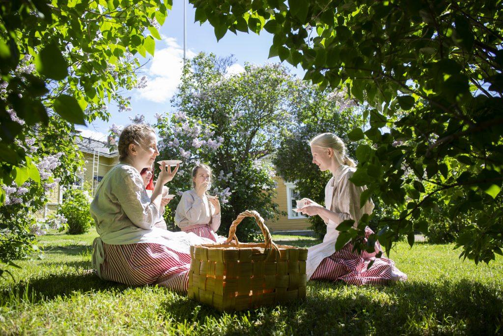 Neljä piioiksi pukeutunutta naista tai tyttöä kahvinjuonnissa korttelimuseon pihalla. Syreenit kukkivat taustalla. Etualalla punottu kori.