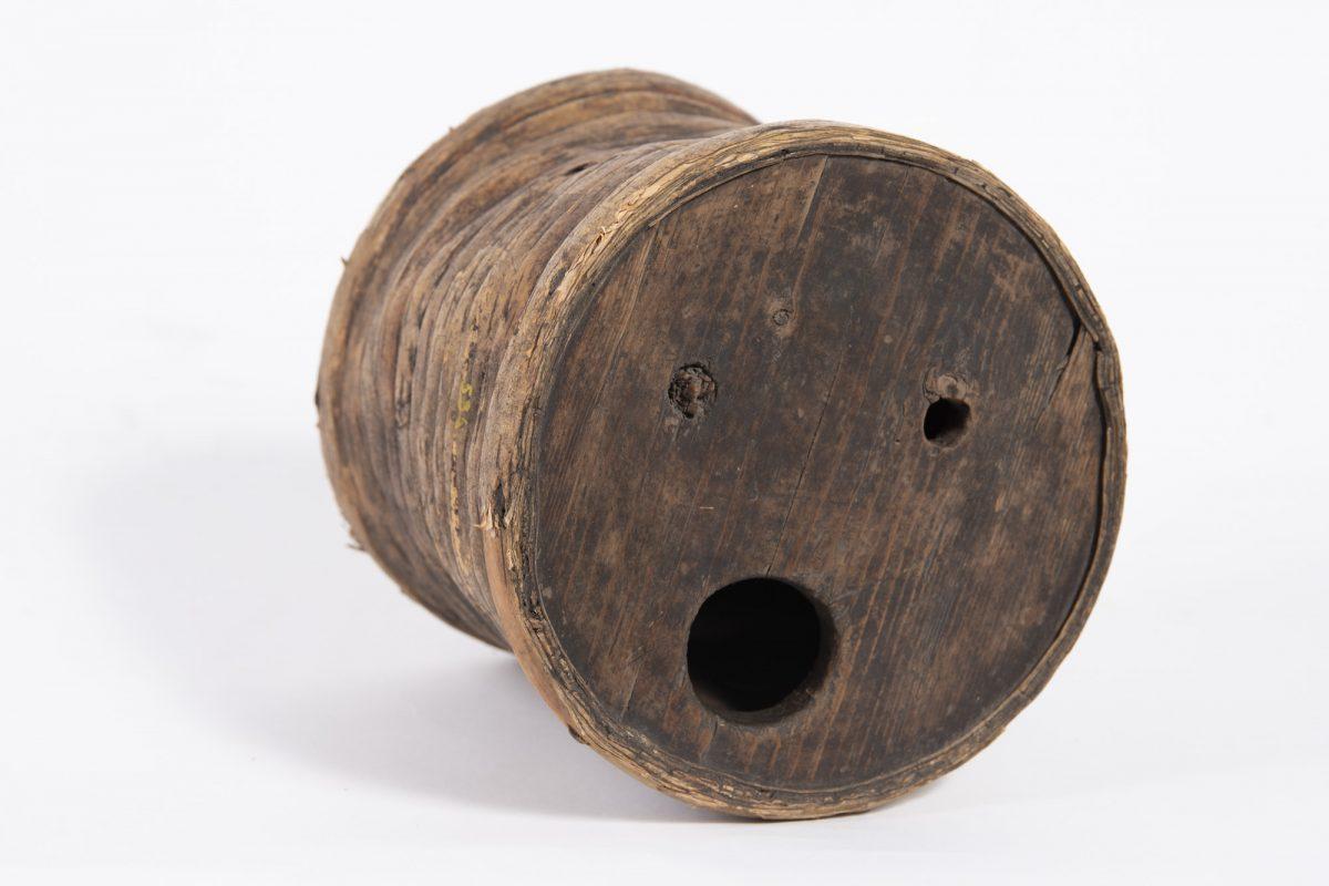 Tumma, puinen astia jonka päädyssä kolme reikää.
