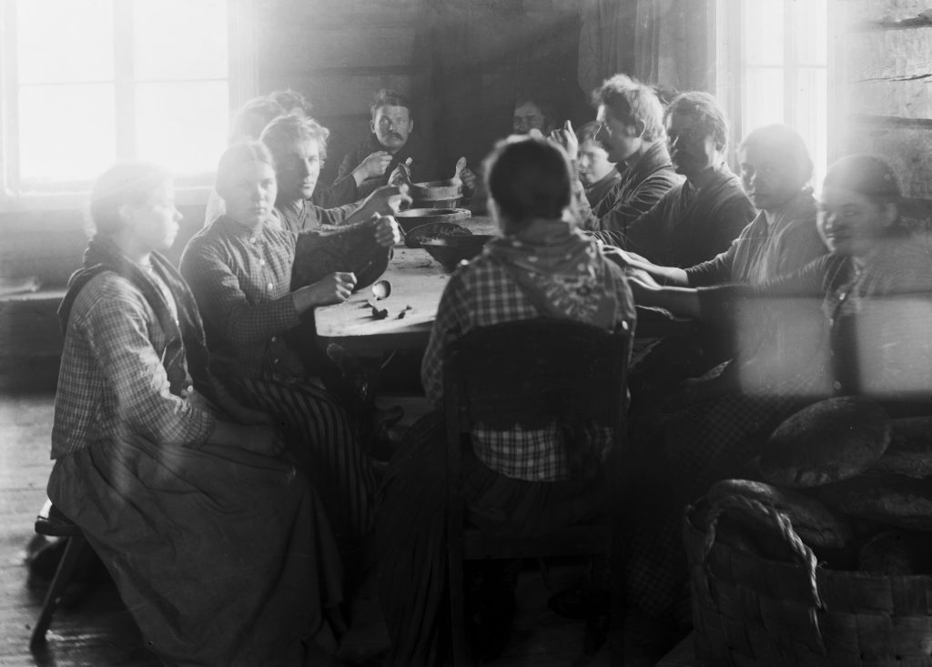 Mustavalkokuva. Pitkään pöytään kokoontunut paljon ihmisiä syömään. Pöydän päässä mies katsoo kameraan.